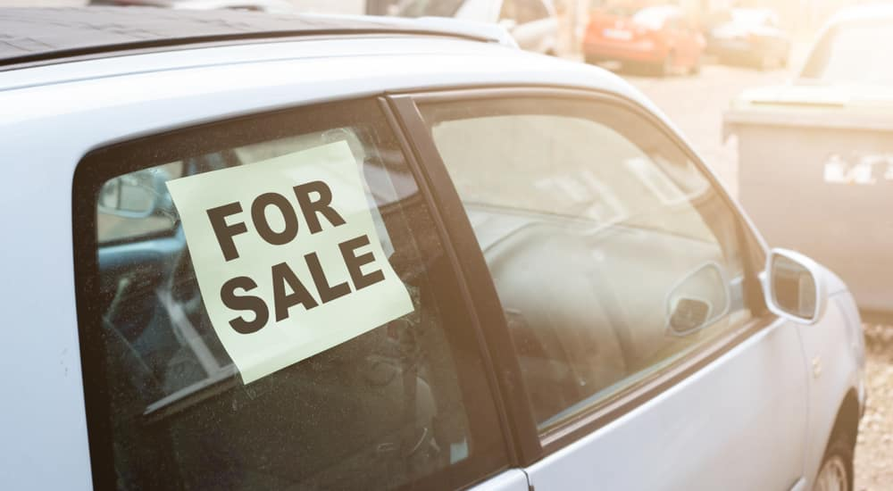 """White car with a black and white """"FOR SALE"""" sign in the back passenger side window"""