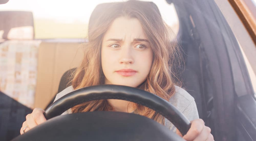 Woman with brown hair in a grey shirt sitting in a vehicle with her hands on the wheel and a concerned look on her face