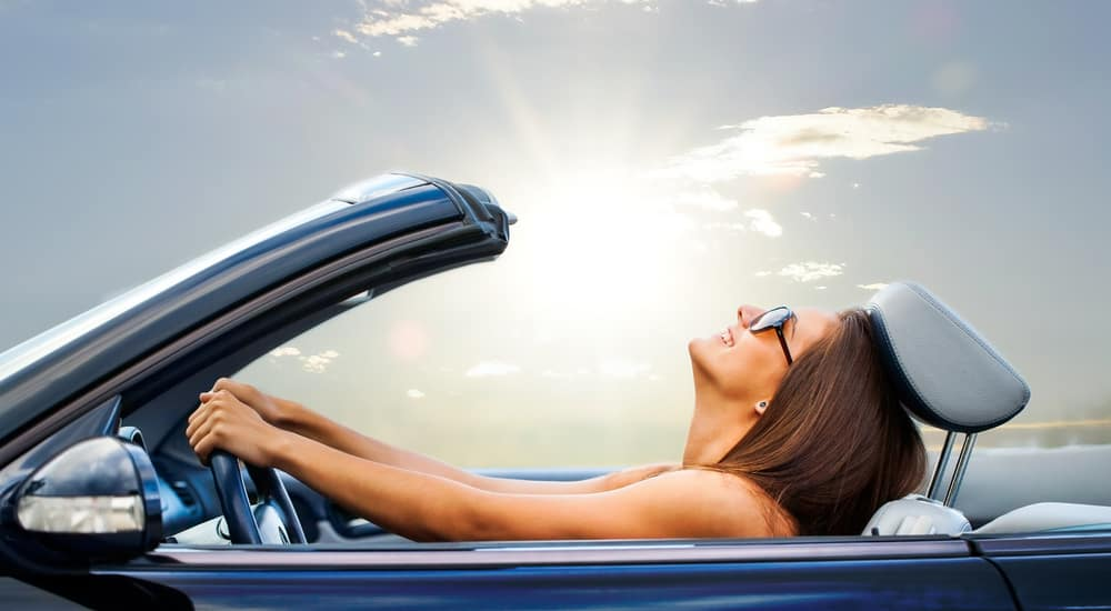 Woman in sunglasses with her head toward the sky driving a blue convertible with the sun shining in the back
