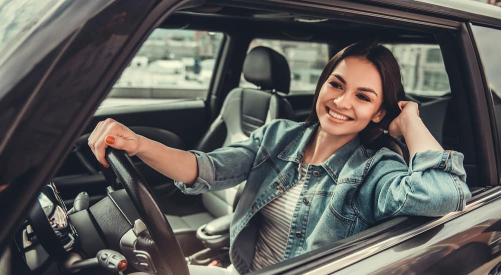 Woman in a jean jacket smiling out the driver's side window of a black vehicle with her right hand on the wheel