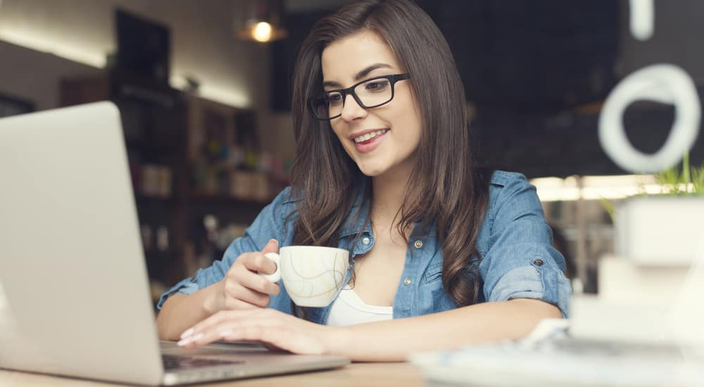 Woman in glasses and a blue shirt holding a mug and using a silver laptop next to a stack of books