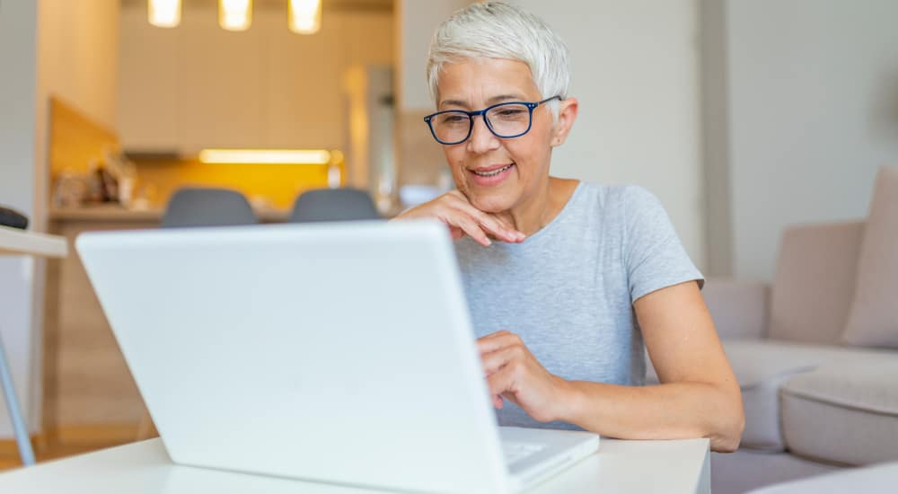 Woman with short hair and glasses sitting at a white desk in front of a beige couch and a kitchen using a white laptop