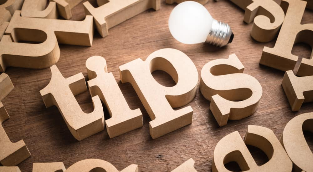 """Lightbulb next to wooden letter blocks scattered on a wooden table with center letters spelling the word """"TIPS"""""""