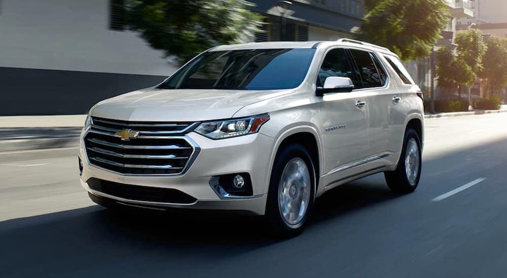 A white 2020 Chevy Traverse is shown driving down a highway after leaving a Cincinnati used car dealership.