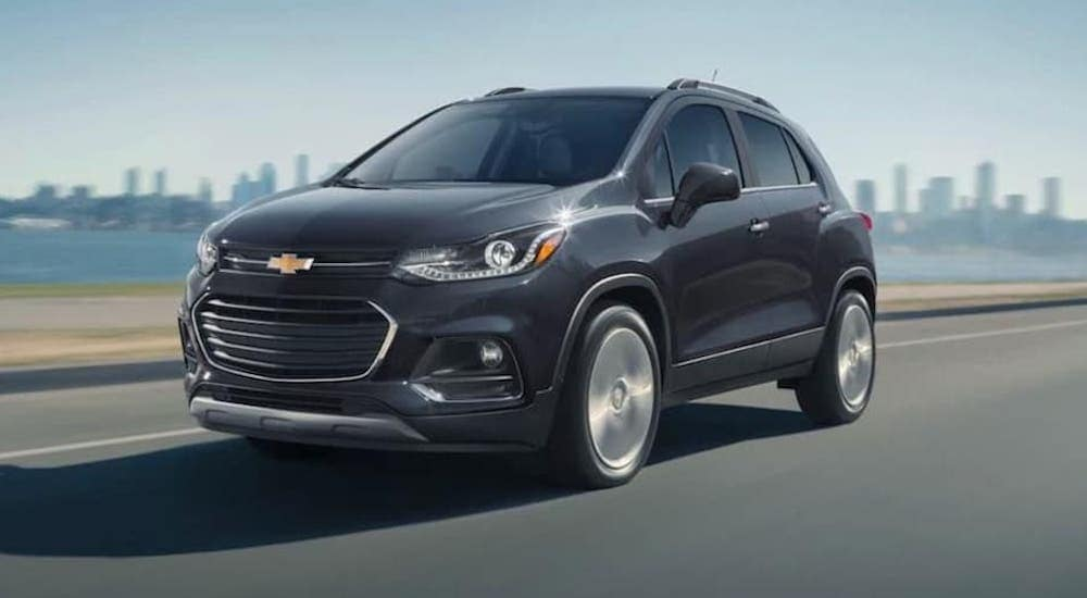 A black 2020 Chevy Trax is shown driving past a city.
