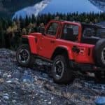 A red 2020 Jeep Wrangler Rubicon is shown from the back parked on rocks in the mountains.