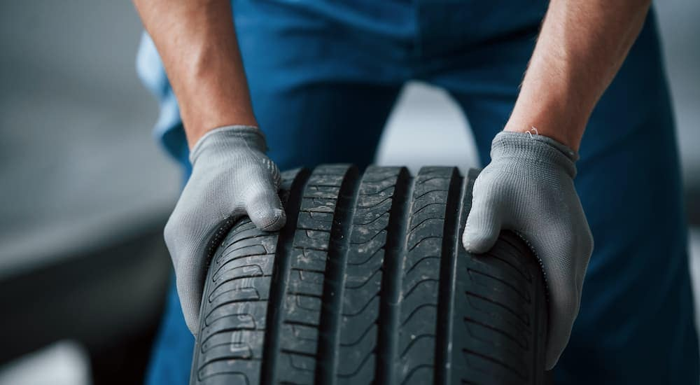 A gloved mechanic is shown rolling a tire after a customer searching for 'cheap tires Cincinnati.'