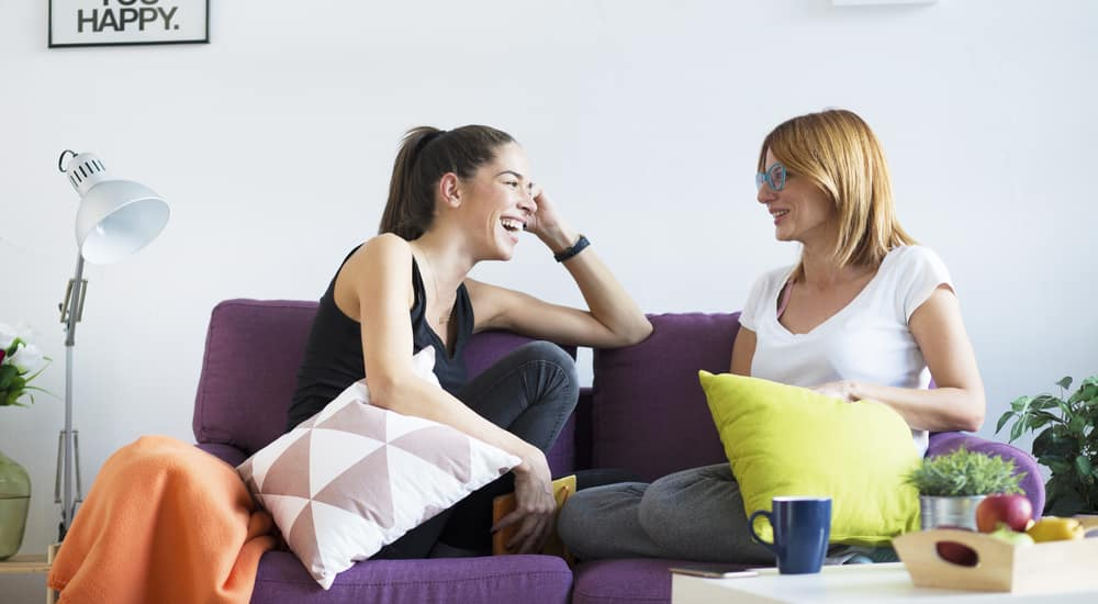 Two happy young female friends conversing in the living room at home