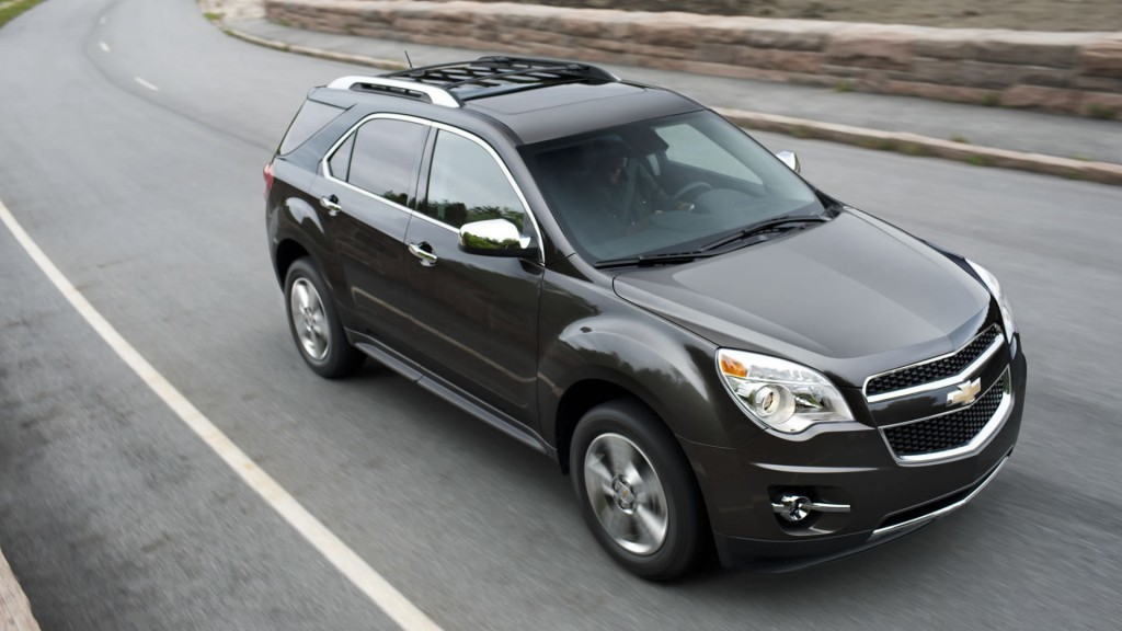 A black Chevy Equinox on a road in front of a stone wall