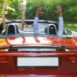 Happy free couple driving in red retro car cheering joyful with arms raised