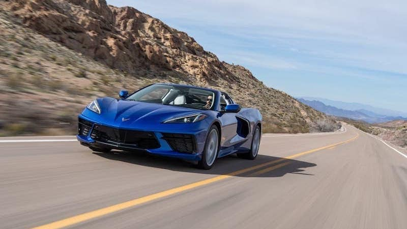 A blue 2020 Chevy Corvette Stingray is driving on a desert highway.