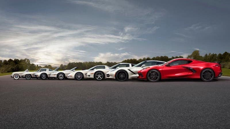 8 generations of Chevy Corvette are shown, 7 of them are silver and the 2020 model is red and closest to the camera.