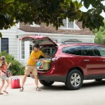A family loading up a red Chevy Traverse
