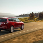 A red Chevy Traverse driving by a lake