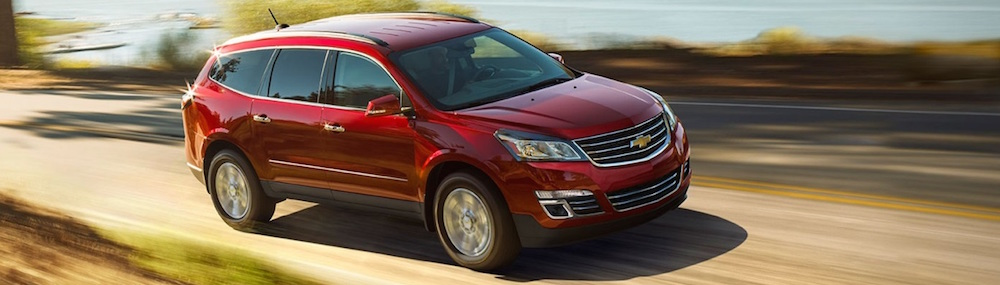 A red 2016 Chevy Traverse is driving on a rural road near Cincinnati, OH.