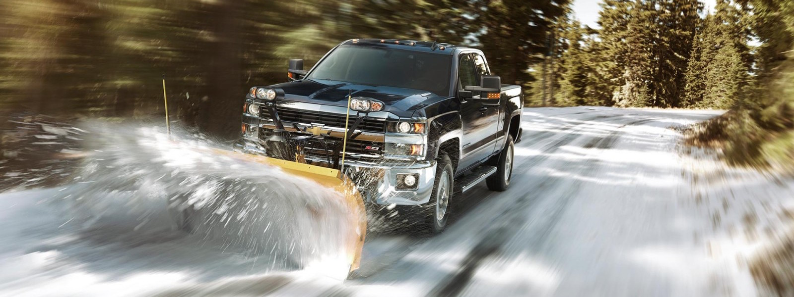 A black 2016 Chevy Silverado is plowing snow on a woodland road.