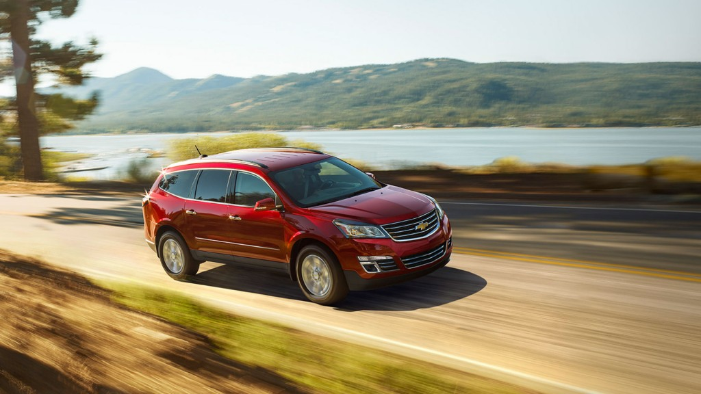 A red 2016 Chevy Equinox is driving past a lake after winning the 2016 Chevy Traverse vs 2016 Ford Explorer comparison.