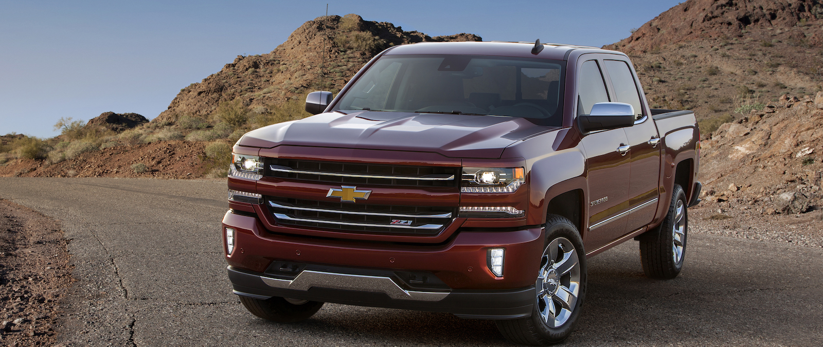 A red 2016 Chevy Silverado 1500 LTZ Z71 is parked on a desert road.