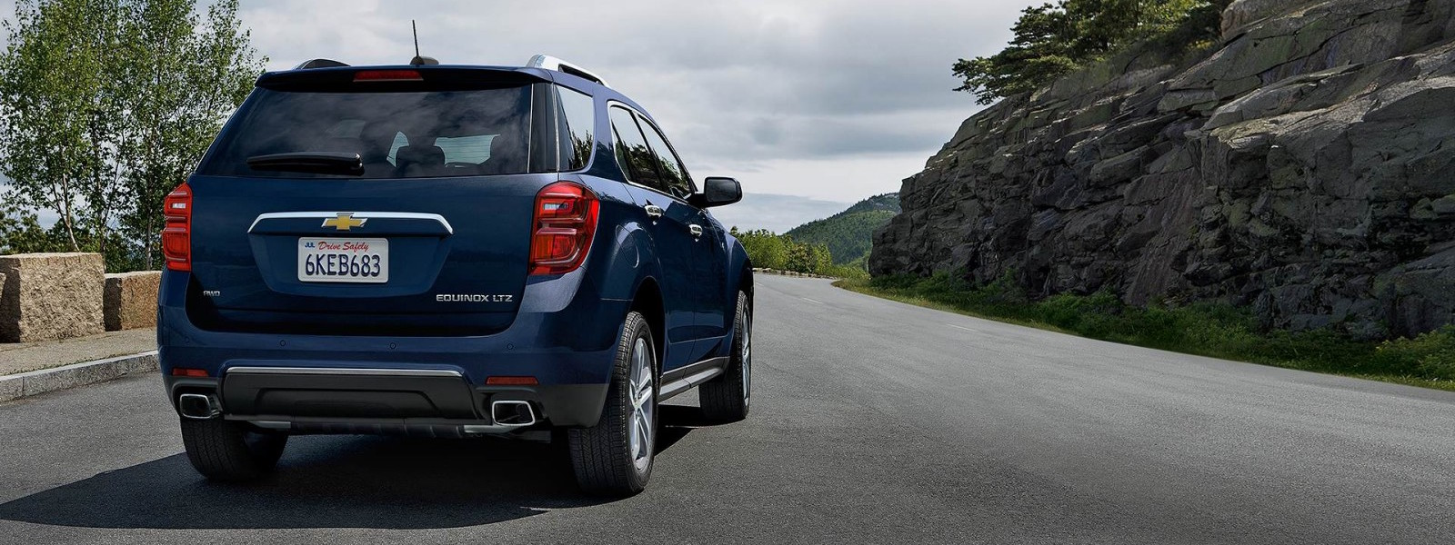 Blue 2016 Chevy Equinox driving down cliffside road