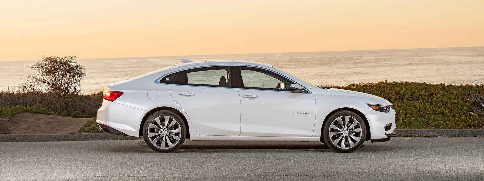 White 2016 Chevy Malibu driving along a beach sunset