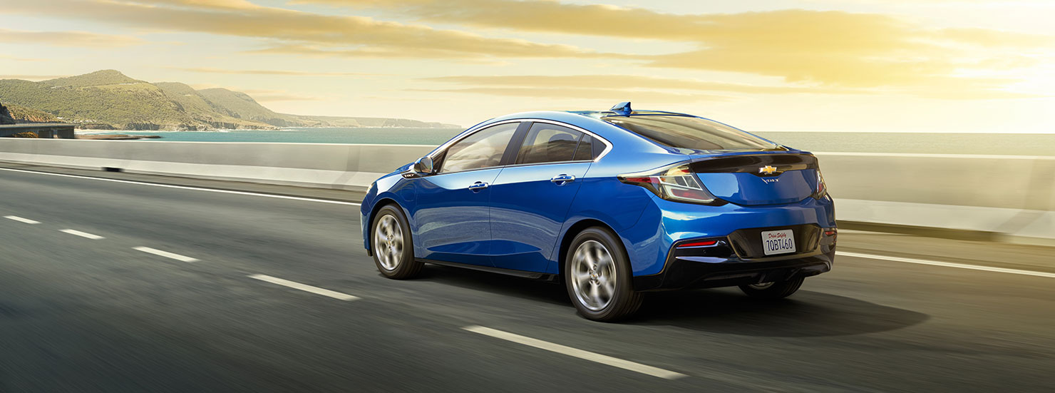 A blue 2017 Chevy Volt is driving down road.