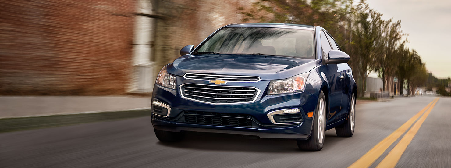 One of the many cars for sale in Cincinnati, a blue Chevy Cruze is driving on an Ohio street.