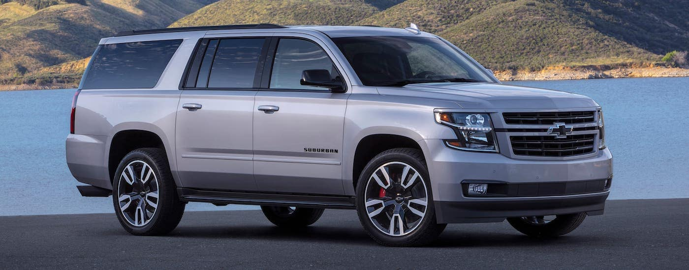 A silver 2019 Chevy Suburban RST is parked in front of a lake.