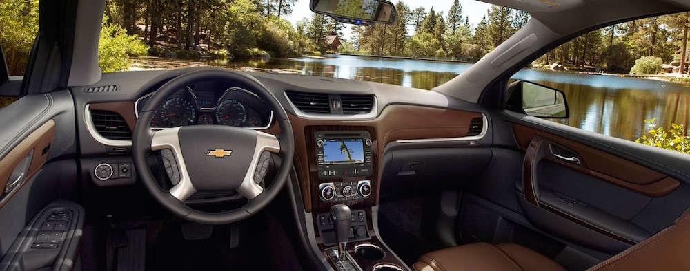 The brown and black interior if a 2016 Chevy Traverse is shown from the inside and a pond is seen through the windshield.
