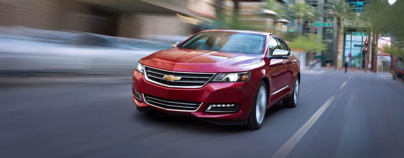 A red 2018 Chevy Impala is driving on an Indianapolis street.