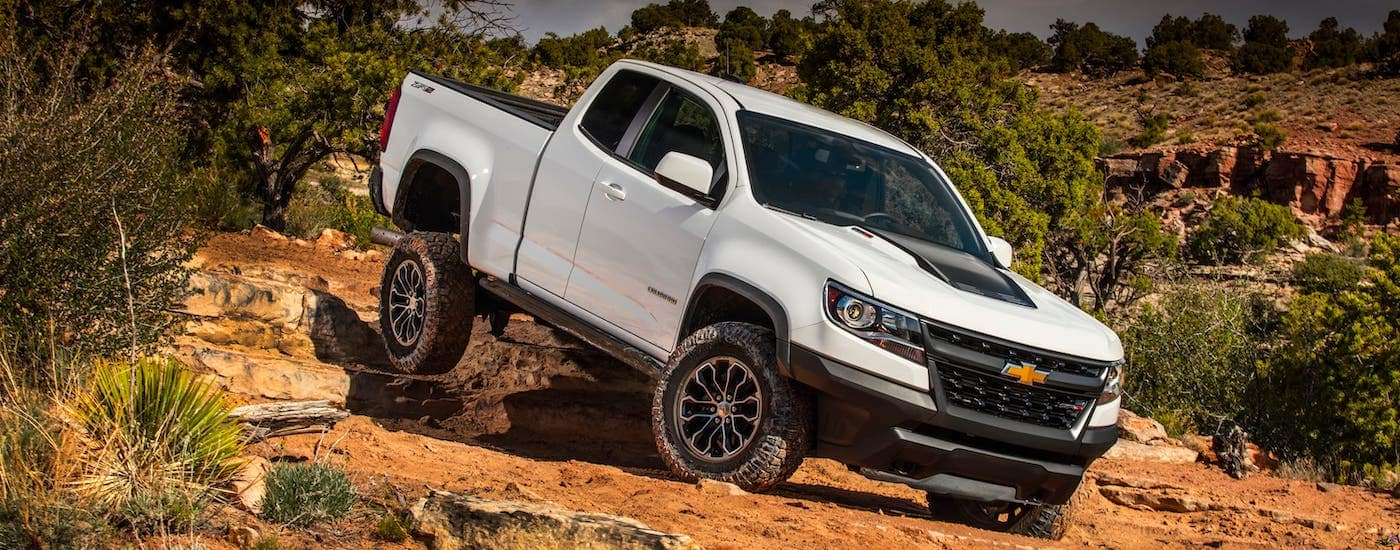 A white 2017 Chevy Colorado ZR2 is climbing over rocks.
