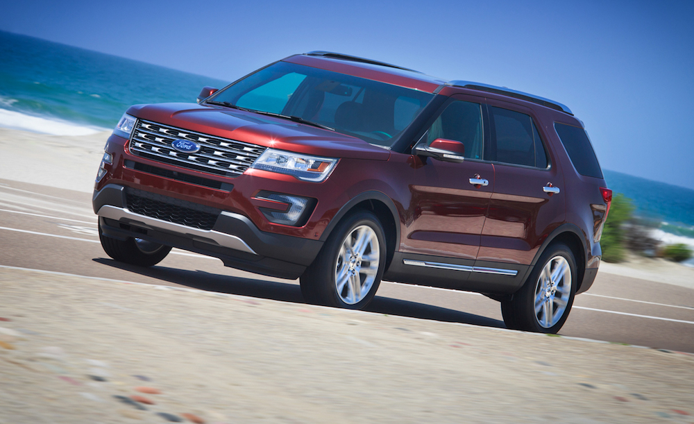 A red 2016 Ford Explorer is driving past the ocean.