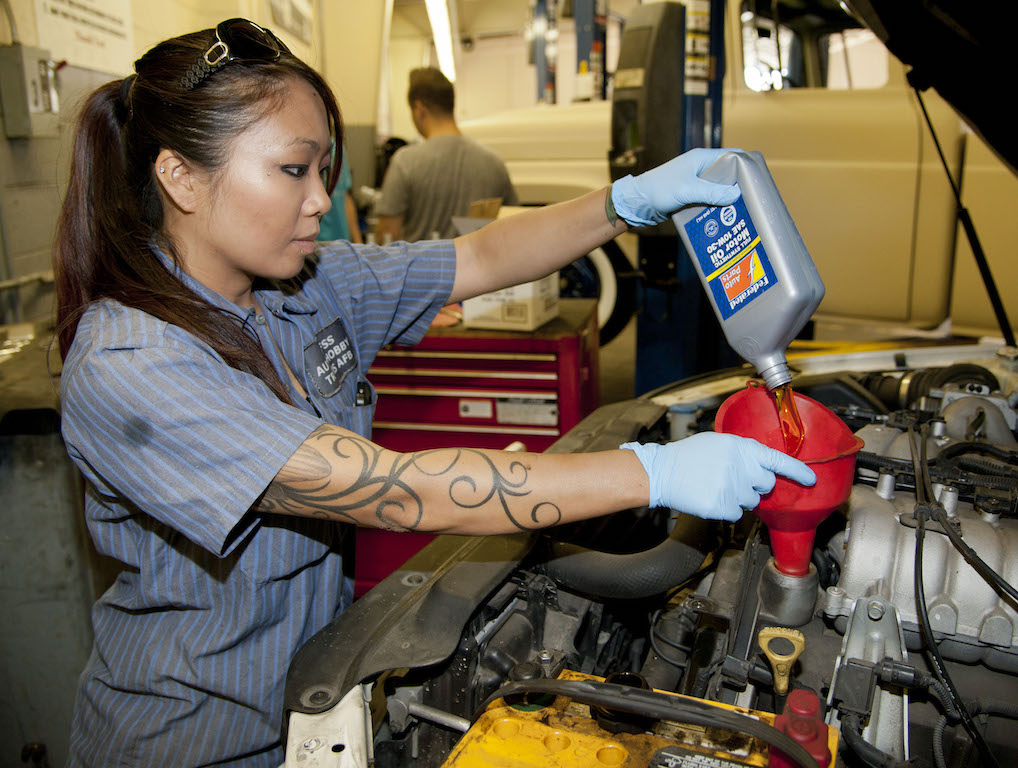 Liz Jacob, 60th Force Support Squadron Auto Hobby Shop automotive technician, finishes a customer's oil change by putting fresh oil into the vehicle Tuesday. With PLAYpass, members can take oil change and tire rotation classes at the Auto Hobby Shop. (U.S. Air Force photo/Airman 1st Class Nicole Leidholm)
