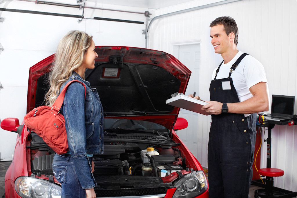 A mechanic talking to a woman in front of a car