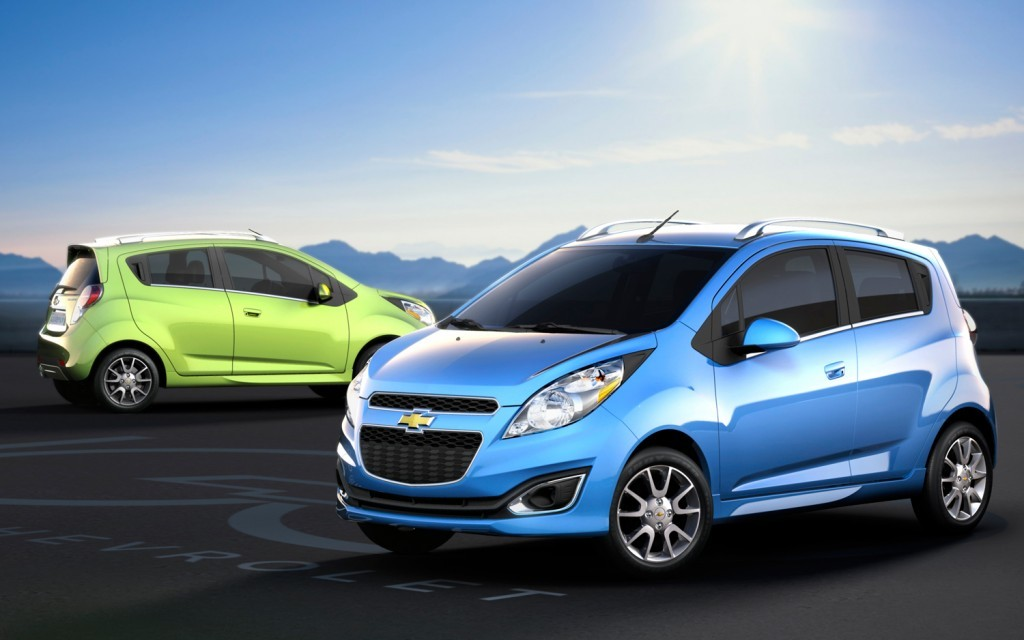 A blue and a green Chevy Spark are parked in an empty lot with mountains in the distance.