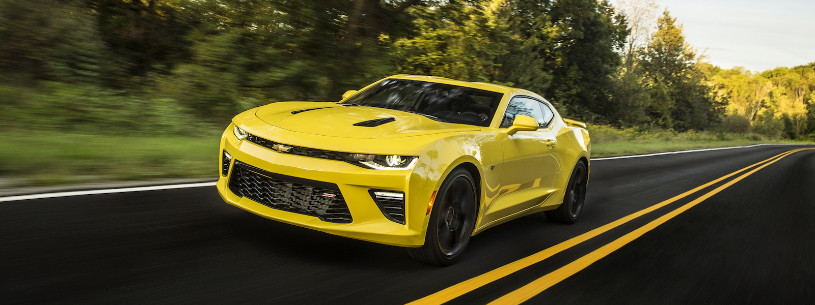 A yellow 2016 Chevy Camaro driving down a scenic road with trees in the background.