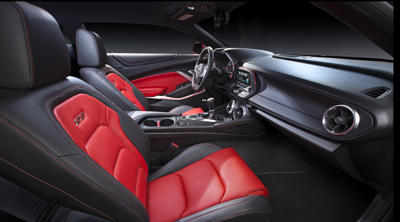 The inside of a 2016 Chevy Camaro with black and red interior.