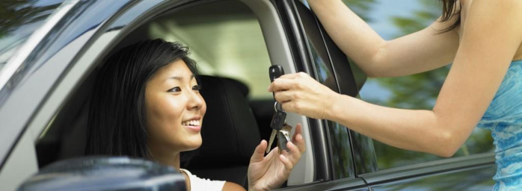 A woman handing car keys to a woman inside a car
