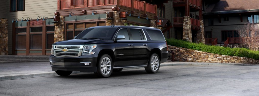 A black 2016 Chevy Suburban is parked in front of a modern home, check one out at Chevy dealers in Ohio.