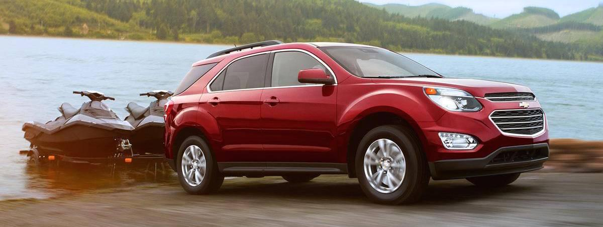 A red 2017 Chevy Equinox is pulling two jet-skis out of a lake.