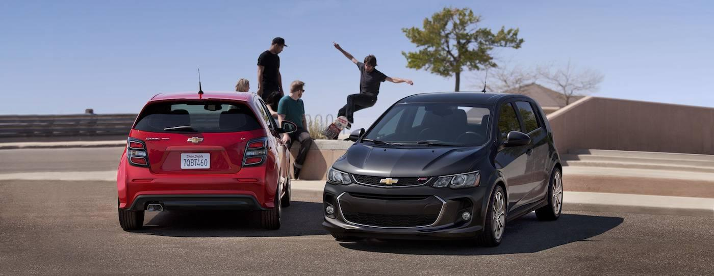 A red and a gray 2017 Chevy Sonic Hatchbacks are at a skatepark in front of skateboarders.