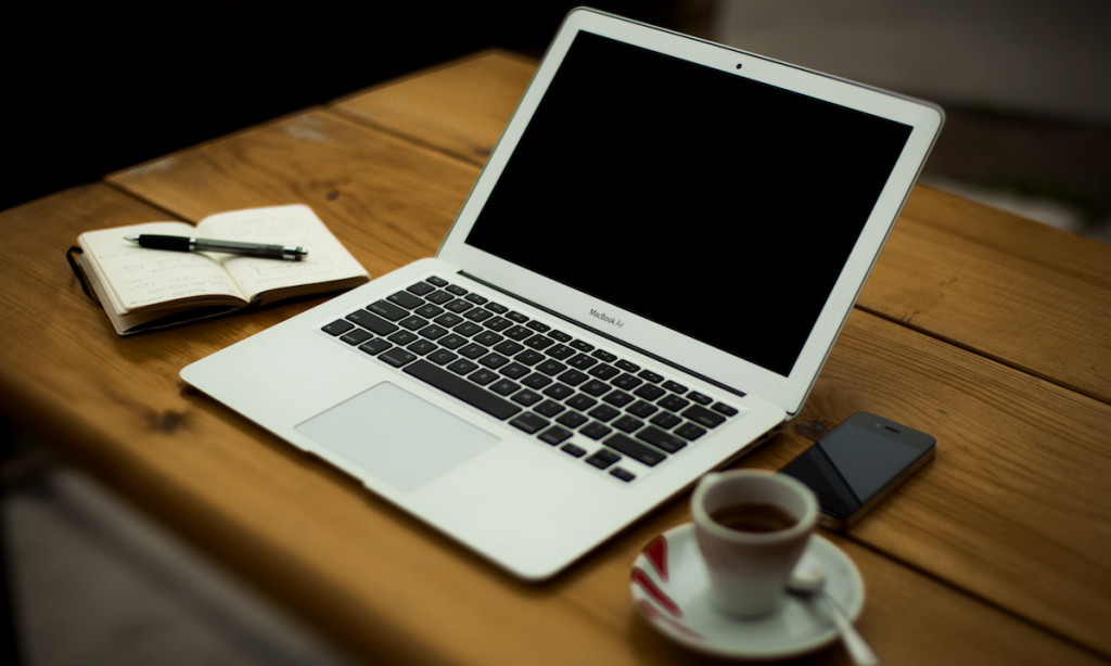 A laptop sitting on a table with a phone, coffee, journal and pen