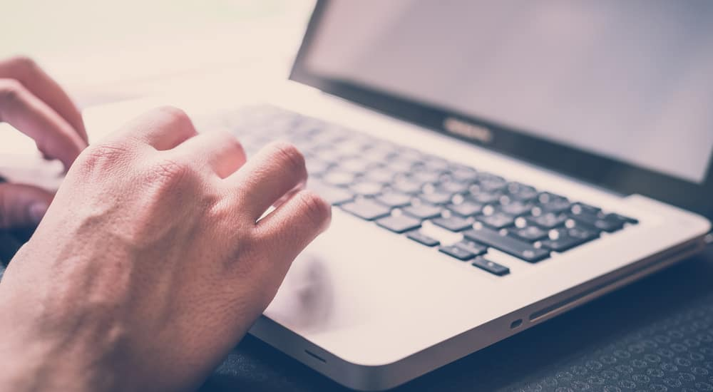 A closeup is shown of hands on a laptop using the used car finder tool at McCluskey Chevrolet.