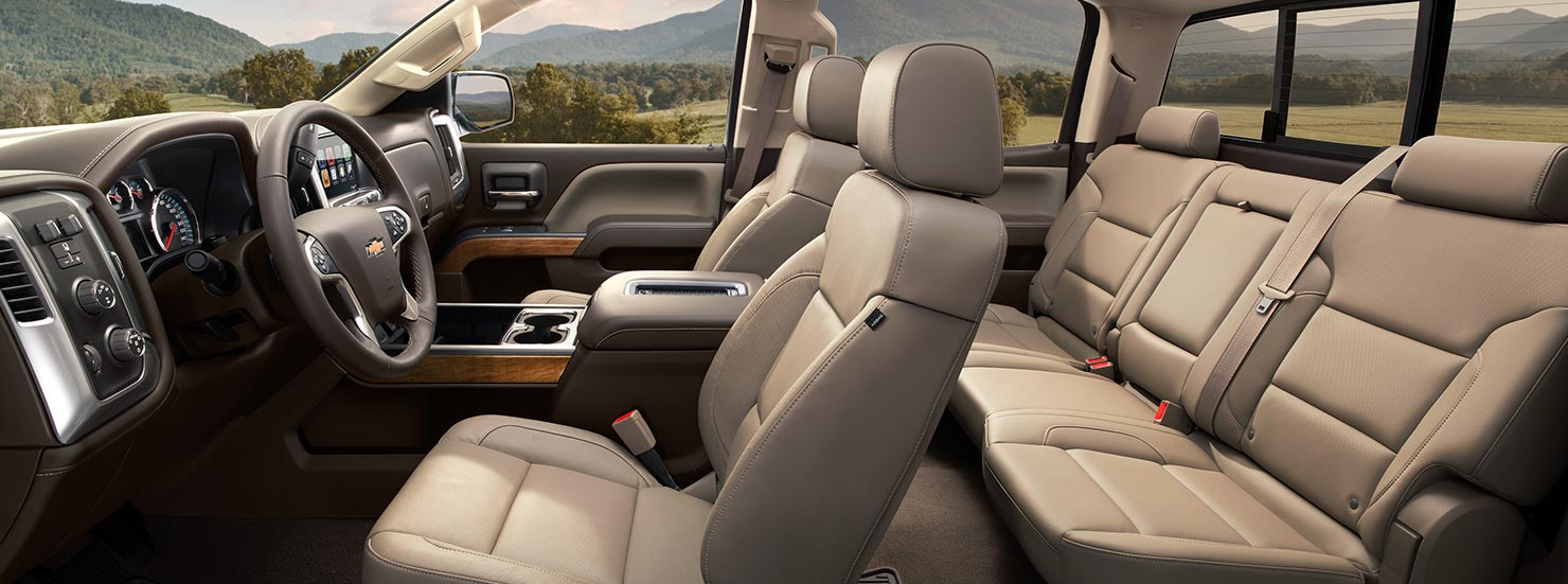 A side interior look at the light tan leather seats in a 2017 Chevy Silverado.