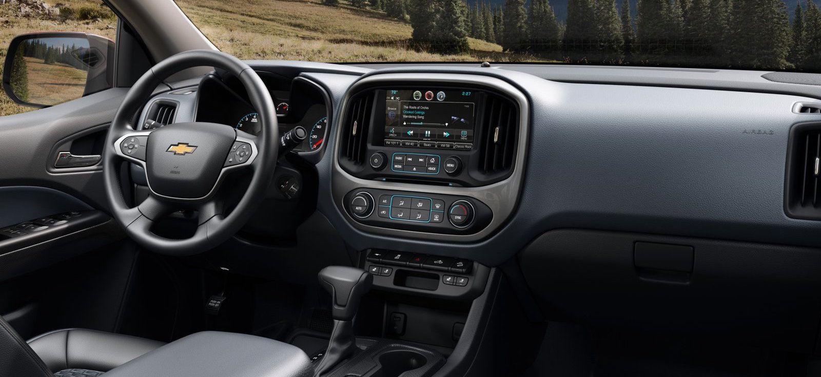 Black interior in the front of the 2017 Colorado, a touchscreen, and other tech are shown.