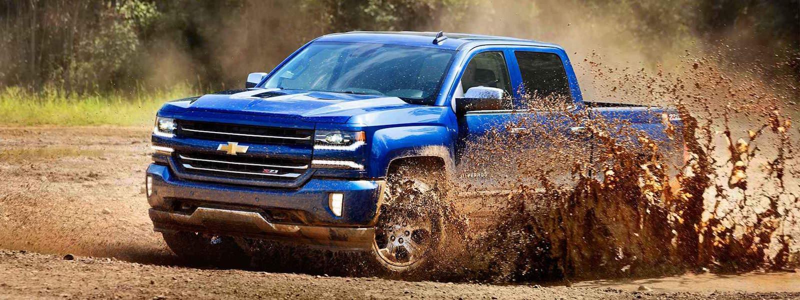 A blue Chevy Silverado is driving through a mud puddle near Cincinnati, OH.