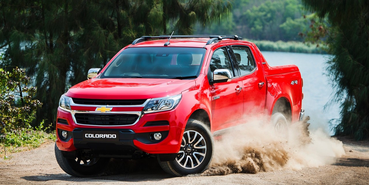 A red 2016 Chevy Colorado is driving on a dirt road while dust is flying in the air.