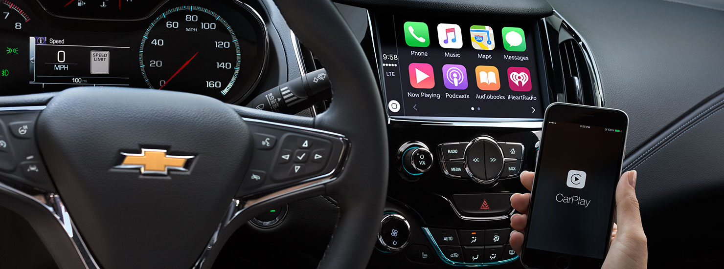 The front dashboard touchscreen with other high tech equipment is shown with someone holding an iPhone in their 2017 Cruze.