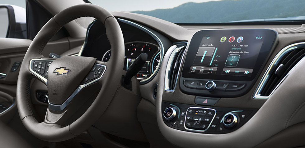 A front interior look of the 2017 Chevy Malibu is shown with black and grey trim with a touchscreen.