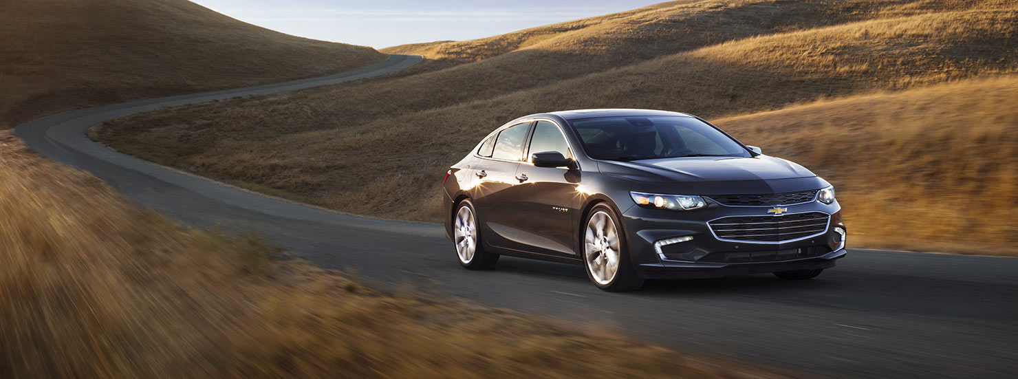 A black 2017 Chevy Malibu is driving by fields outside of Cincinnati, OH.