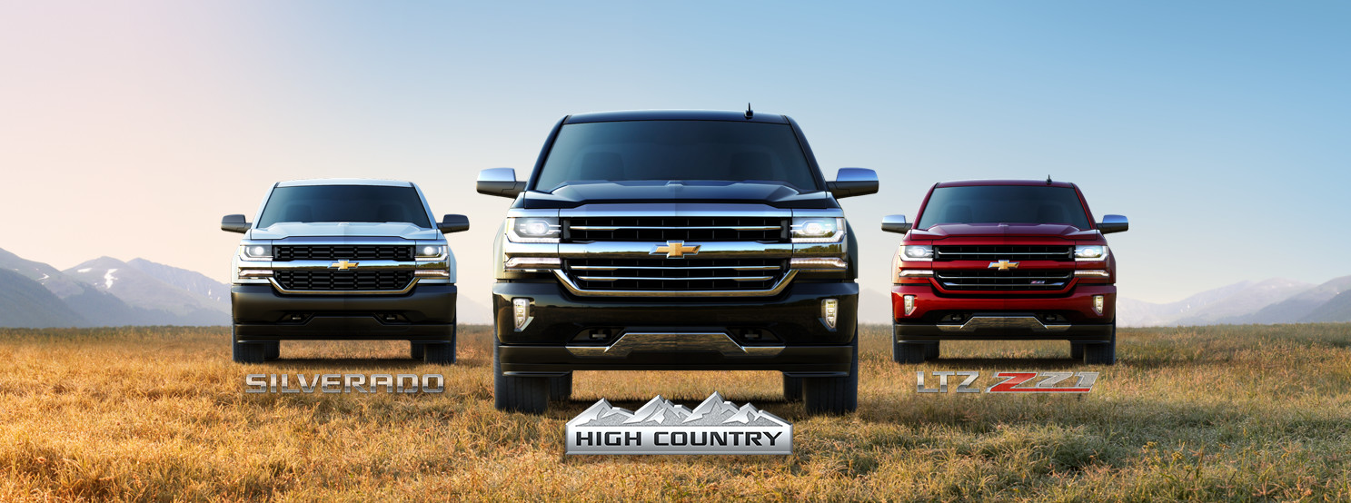 3 trim levels of the 2017 Chevrolet Silverado are parked in a hay field.